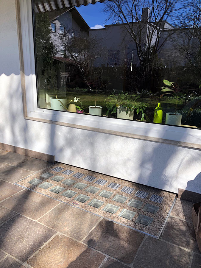 Isartaler Lichtschacht-Abdeckung auf Naturstein-Terrasse