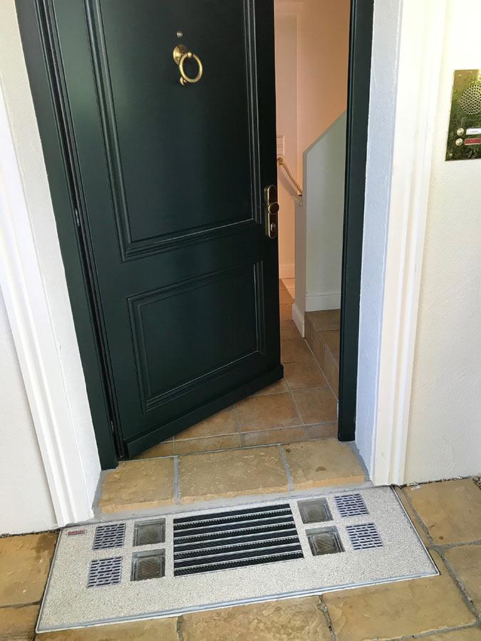 Lichtschacht-Abdeckung im Eingangsbereich mit Fußmatte